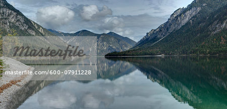 Scenic view of mountains reflected in a clear lake (Plansee) in autumn, Tirol, Austria