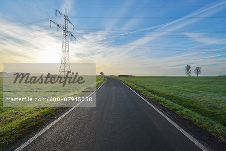 Country Road with Electricity Pylon in Morning with Sun, Freiensteinau, Vogelsbergkreis, Hesse, Germany Stock Photo - Premium Royalty-Free, Image code: 600-07945038