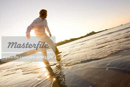 Man skipping rocks in the water at Bailey's Beach on an autumn morning, Newport, Rhode Island, USA Stock Photo - Premium Royalty-Free, Image code: 600-07945073