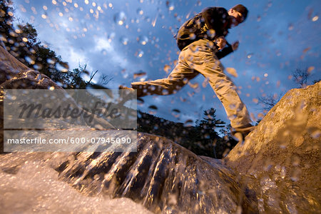 Low angle view of man jumping over a stream while hiking in New Hampshire, USA Stock Photo - Premium Royalty-Free, Image code: 600-07945090