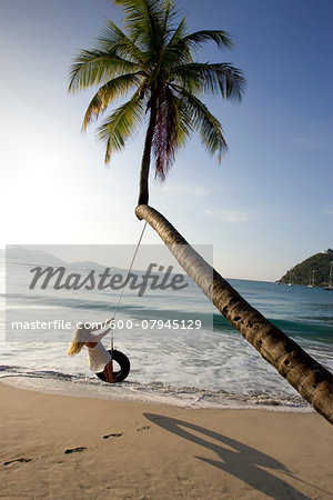 Woman playing on a tire swing on the beach in Cane Garden Bay, Tortola, British Virgin Islands, Caribbean Stock Photo - Premium Royalty-Free, Image code: 600-07945129