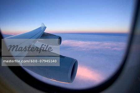 An aircraft wing and engines as seen from the window of a jet while flying above the clouds at sunset. Stock Photo - Premium Royalty-Free, Image code: 600-07945140