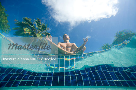 Man doing yoga poolside, view from underwater, Antigua, Caribbean Stock Photo - Premium Royalty-Free, Image code: 600-07945145