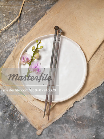 Orchid Flower on White Plate with Chopsticks on Canvas Cloth and Slate Background, Studio Shot Stock Photo - Premium Royalty-Free, Image code: 600-07945379