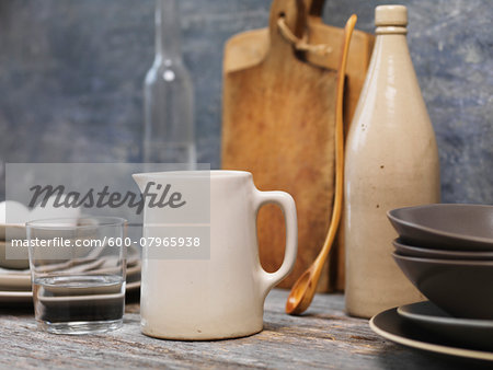 Still life of water jug, with glass of water, wooden spoon, cutting boards, eggs and grey plates. Stock Photo - Premium Royalty-Free, Image code: 600-07965938