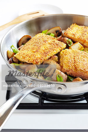 Cornmeal crusted trout fillets in a skillet with potatoes, mushrooms and green onions on a gas stove, studio shot Stock Photo - Premium Royalty-Free, Image code: 600-08002099