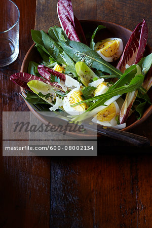 Leafy green salad with boiled egg and parmesan in a wood bowl, studio shot on dark, wooden background