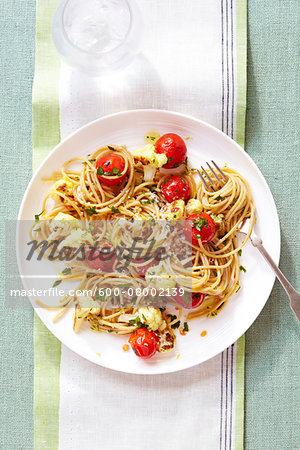 Spaghetti with Tomatoes and Roasted Cauliflower, on a plate with a fork, on a cloth napkin, studio shot Stock Photo - Premium Royalty-Free, Image code: 600-08002139