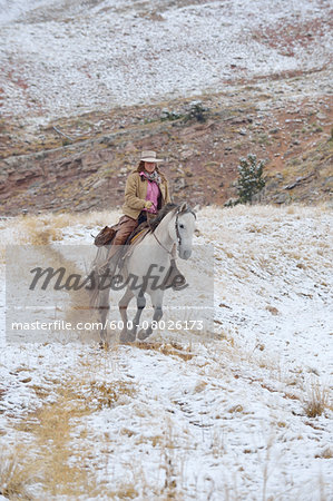 Cowgirl riding horse in snow, Rocky Mountains, Wyoming, USA Stock Photo - Premium Royalty-Free, Image code: 600-08026173