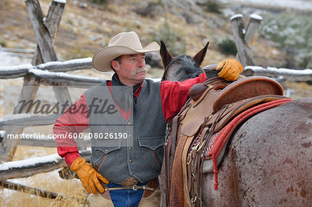 Portrait of Cowboy Standing near Horse, Rocky Mountains, Wyoming, USA Stock Photo - Premium Royalty-Free, Image code: 600-08026190