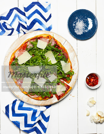 Overhead View of Pizza on Wooden Cutting Board with Bowl of Chili Sauce, Garlic Cloves, Dish with Salt, and Napkin Stock Photo - Premium Royalty-Free, Image code: 600-08060050