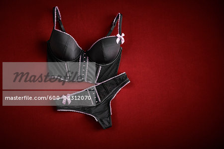 Bustier and thong on red background in studio Stock Photo - Premium Royalty-Free, Image code: 600-08312070
