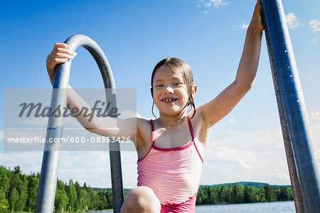 Young girl in swim suit climbing ladder out of lake, Sweden Stock Photo - Premium Royalty-Free, Image code: 600-08353426