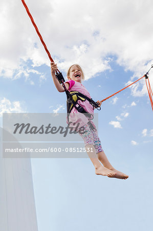 6 year old girl jumping with a bungee trampoline on a sunny day, Germany Stock Photo - Premium Royalty-Free, Image code: 600-08512531