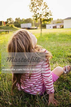 5 year old girl sitting on the grass on a sunny evening and staring at the sky, Germany Stock Photo - Premium Royalty-Free, Image code: 600-08512533