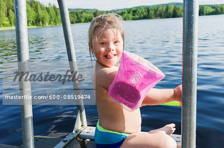 Girl with Down Syndrome wearing Water Wings Sitting on Jetty of Lake, Sweden Stock Photo - Premium Royalty-Free, Image code: 600-08519474