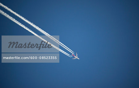 Airplane and contrails against blue sky, Canada Stock Photo - Premium Royalty-Free, Image code: 600-08523355