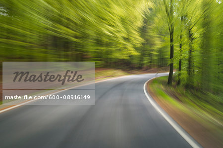 Driving along paved road through the spring forest at Amorbach in Odenwald, in Lower Franconia, Bavaria, Germany
