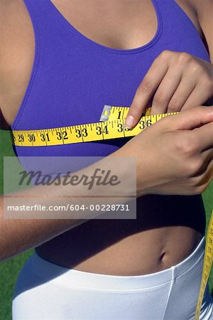 Woman measuring bust Stock Photo - Premium Royalty-Free, Image code: 604-00228731