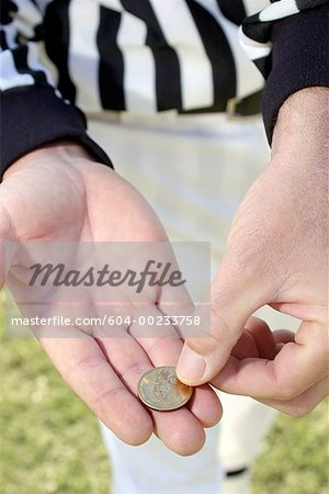 Referees hands with coin/ Stock Photo - Premium Royalty-Free, Image code: 604-00233758