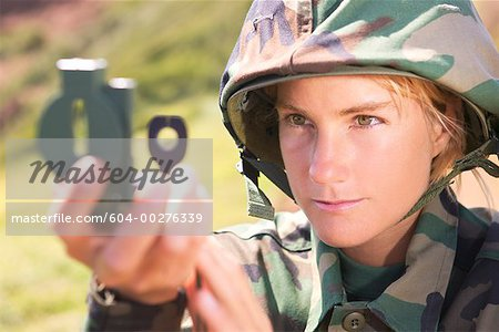 Soldier looking through compass scope Stock Photo - Premium Royalty-Free, Image code: 604-00276339