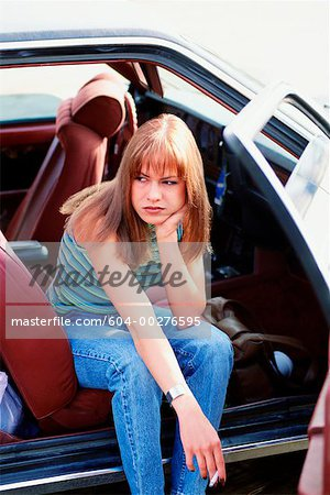 Woman in car with cigarette Stock Photo - Premium Royalty-Free, Image code: 604-00276595