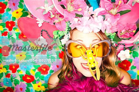 Woman wearing hat and sunglasses with plastic bee on nose Stock Photo - Premium Royalty-Free, Image code: 604-00277107