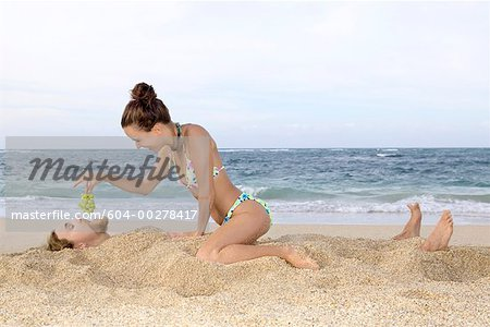 Woman feeding grapes to man buried in sand/ Stock Photo - Premium Royalty-Free, Image code: 604-00278417