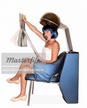 Woman reading magazine under salon hair dryer/ Stock Photo - Premium Royalty-Free, Image code: 604-00278511