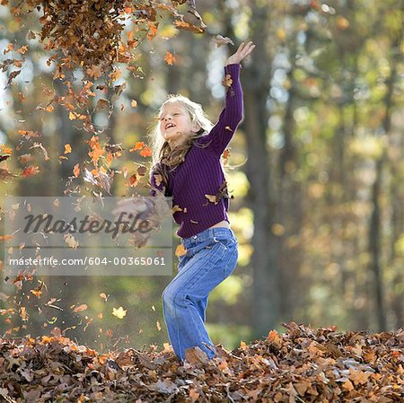 Girl playing in leaves/ Stock Photo - Premium Royalty-Free, Image code: 604-00365061