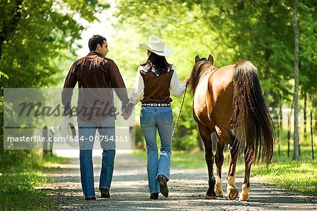 Couple with horse holding hands Stock Photo - Premium Royalty-Free, Image code: 604-00754351