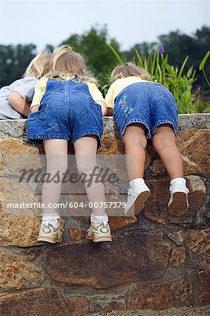 Girls looking over wall Stock Photo - Premium Royalty-Free, Image code: 604-00757379