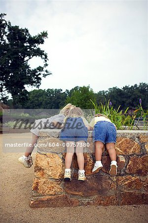 Girls looking over wall Stock Photo - Premium Royalty-Free, Image code: 604-00757380