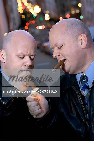 Identical twins smoking cigars Stock Photo - Premium Royalty-Free, Image code: 604-00759610