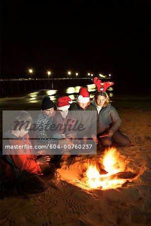 Family around campfire on beach Stock Photo - Premium Royalty-Free, Image code: 604-00760237