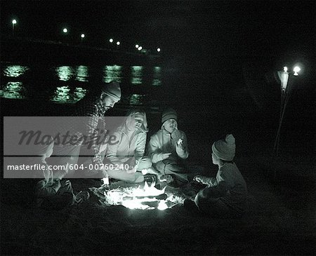 Family around campfire on beach Stock Photo - Premium Royalty-Free, Image code: 604-00760240