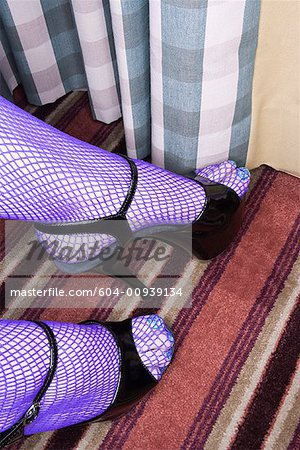 Feet in fishnet stockings/ Stock Photo - Premium Royalty-Free, Image code: 604-00939134