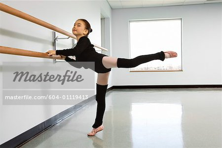 Girl practicing arabesque at the barre in ballet class Stock Photo - Premium Royalty-Free, Image code: 604-01119413