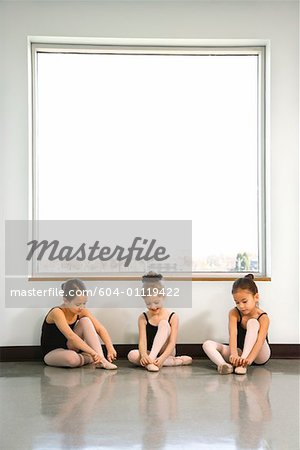 Ballet students sitting by window adjusting slippers Stock Photo - Premium Royalty-Free, Image code: 604-01119422