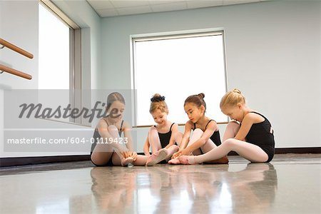 Ballet students adjusting slippers Stock Photo - Premium Royalty-Free, Image code: 604-01119423