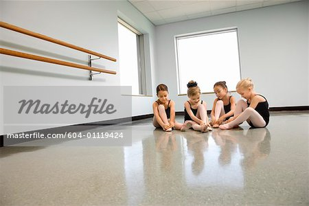 Ballet students adjusting slippers Stock Photo - Premium Royalty-Free, Image code: 604-01119424