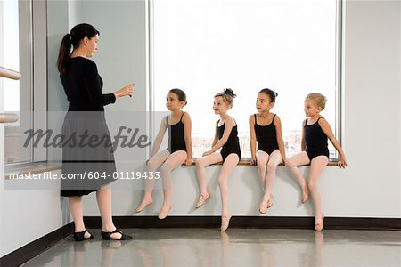 Ballet instructor addressing students sitting in window Stock Photo - Premium Royalty-Free, Image code: 604-01119433