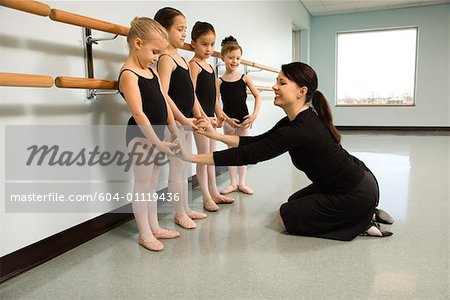 Ballet instructor correcting students Stock Photo - Premium Royalty-Free, Image code: 604-01119436