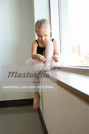 Girl sitting in window adjusting ballet slippers Stock Photo - Premium Royalty-Free, Image code: 604-01119466