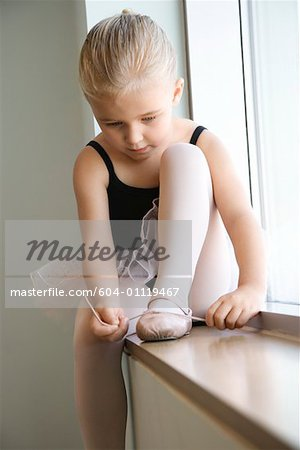 Girl sitting in window adjusting ballet slippers Stock Photo - Premium Royalty-Free, Image code: 604-01119467