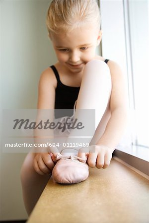 Girl sitting in window adjusting ballet slippers Stock Photo - Premium Royalty-Free, Image code: 604-01119469
