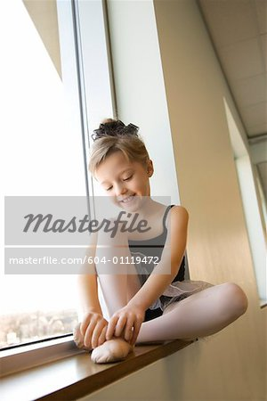 Girl sitting in window adjusting ballet slippers Stock Photo - Premium Royalty-Free, Image code: 604-01119472