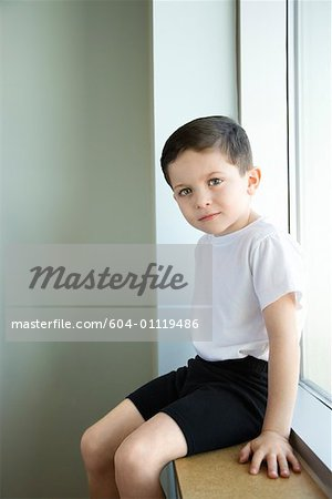 Boy sitting in window sill Stock Photo - Premium Royalty-Free, Image code: 604-01119486