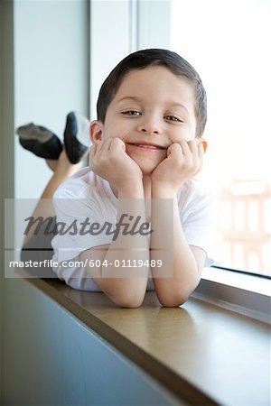 Boy in ballet class lying in window sill Stock Photo - Premium Royalty-Free, Image code: 604-01119489
