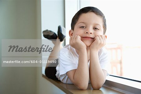 Boy in ballet class lying in window sill Stock Photo - Premium Royalty-Free, Image code: 604-01119490